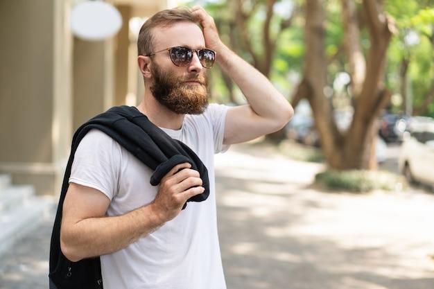 ガールフレンドを待っている物思いにふけるひげを生やした男