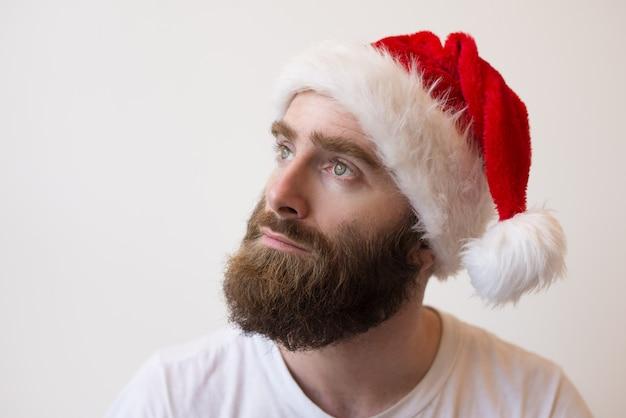 サンタの帽子をかぶって物思いにふけるひげを生やした男