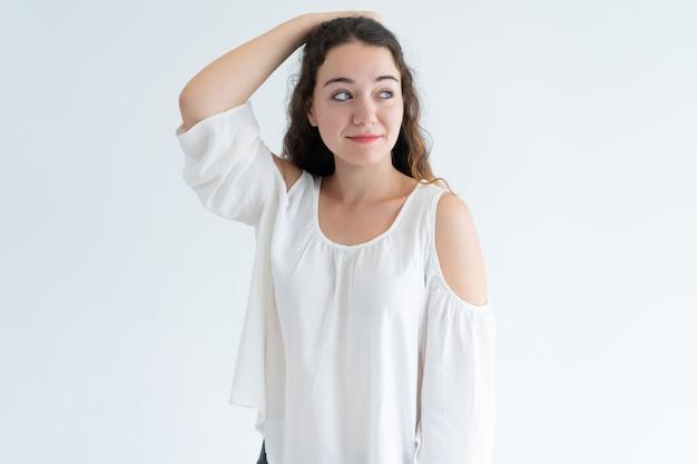 Портрет улыбающегося молодой женщины кавказа, почесывая голову