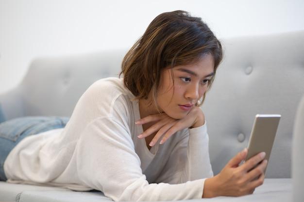 深刻なアジアの電話ユーザーがスマートフォンの画面に焦点を当てて