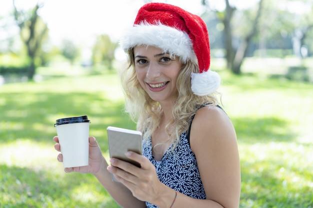 コーヒーとスマートフォンを持って、サンタの帽子をかぶっている笑顔の女性