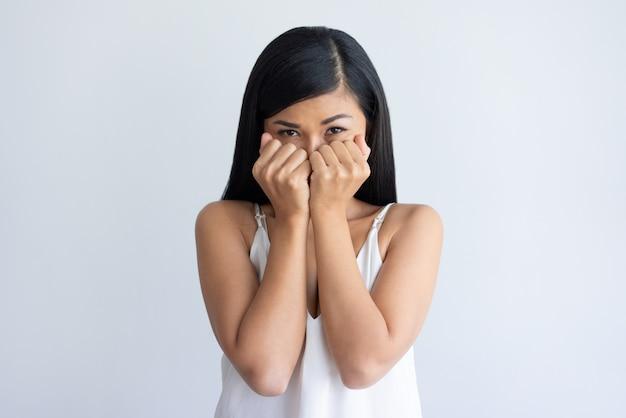 拳の後ろに口を覆っている心配している若いアジア女性