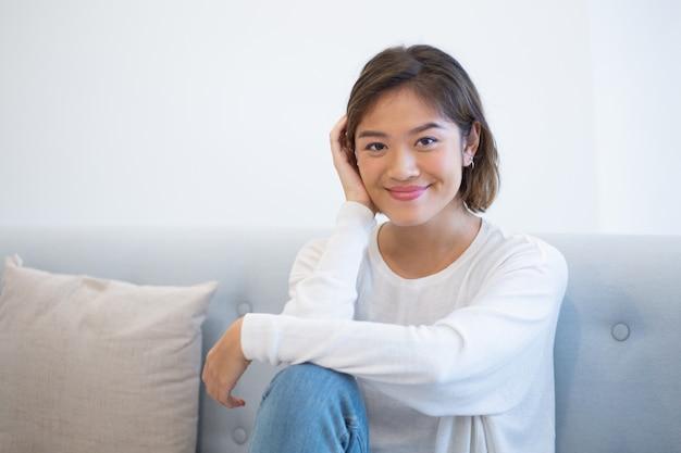 Беззаботная молодая женщина, сидя на тренере дома