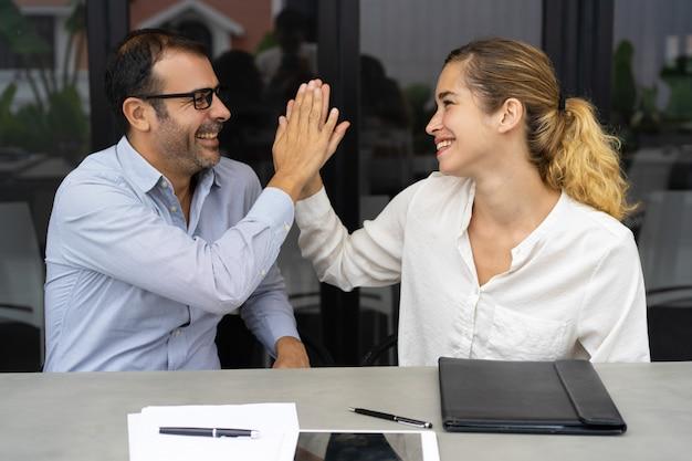Веселые коллеги по бизнесу празднуют успех команды