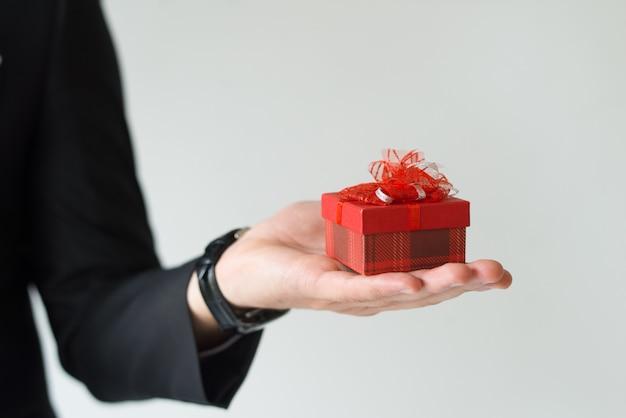 手のひらに小さな贈り物を持って認識できない男のクローズアップ