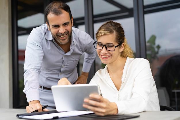 Портрет веселых коллег обсуждают документы на планшете