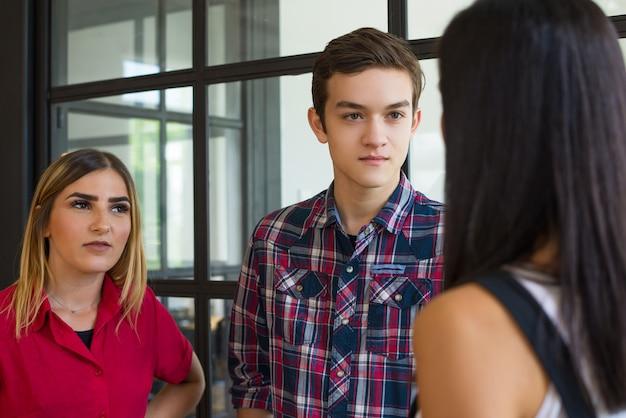 Портрет молодых уверенно студенческих друзей, говорящих на перерыв