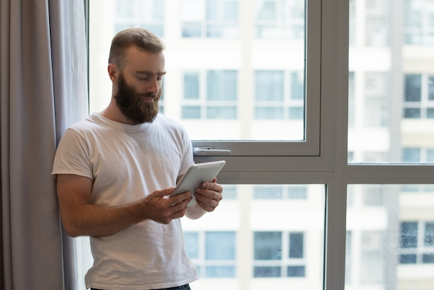自宅でデジタルタブレットを使用して深刻なハンサムな流行に敏感な男