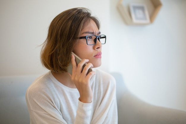 緊張した女性が自宅のソファーでスマートフォンを呼び出す