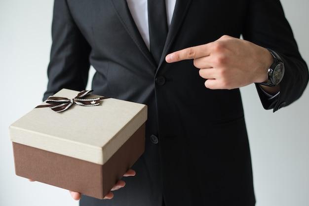 До неузнаваемости бизнесмен держит коричневую подарочную коробку