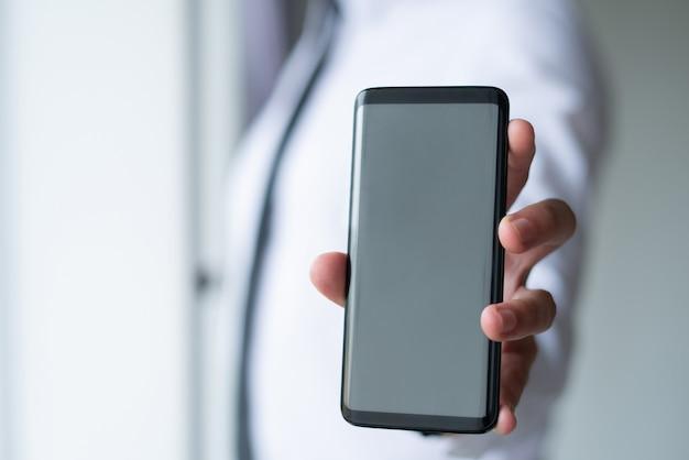 空のスマートフォンの画面を見せてビジネス男のクローズアップ