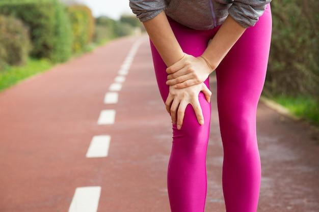 ピンクのタイツを身に着けている、膝を負傷する女性のジョガー