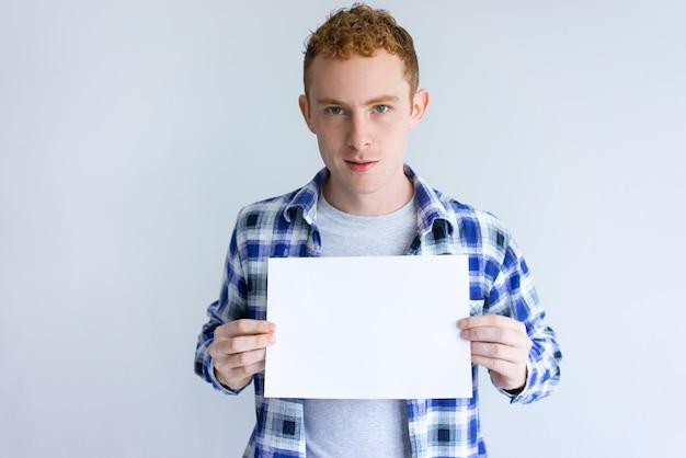 空白の紙のシートを示す焦点を当てた若い男