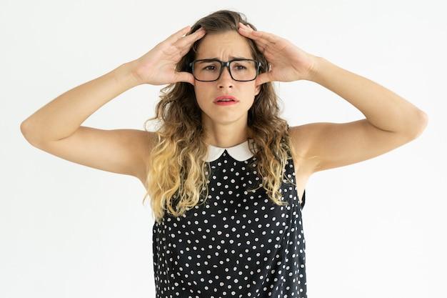Разочарованная милая молодая женщина касаясь голове