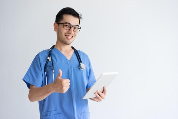 タブレットを押しながら親指を現して幸せな男性医師