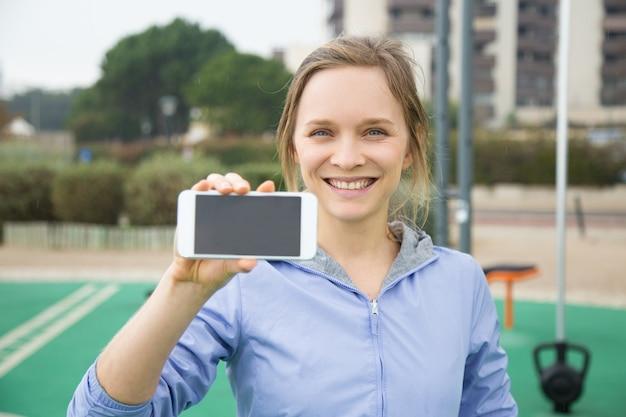 スポーツモバイルアプリを宣伝するハッピースポーティーな女の子