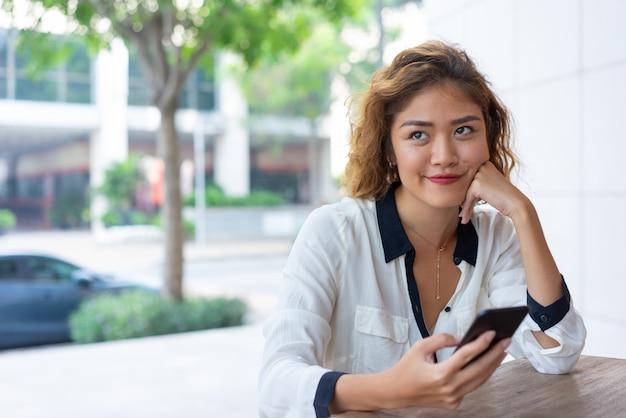 Положительная азиатская девушка офиса отдыхая в уличном кафе