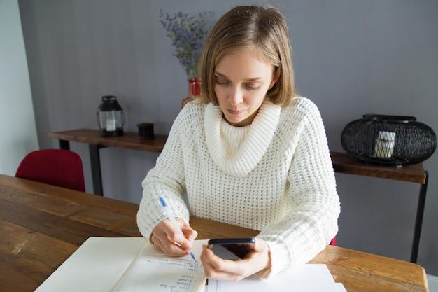 Серьезная молодая женщина записывая задачу в блокноте