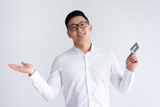クレジットカードを押しながら手を投げて笑顔のアジア人男性