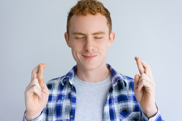 Улыбающийся красивый мужчина показывает жест скрещенные пальцы