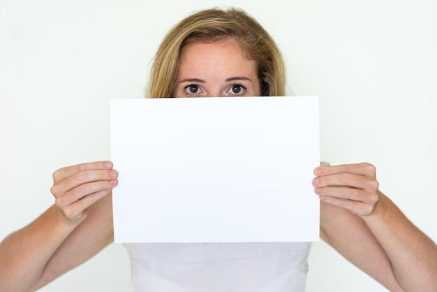 空白の紙のシートの後ろに隠れている若い女性