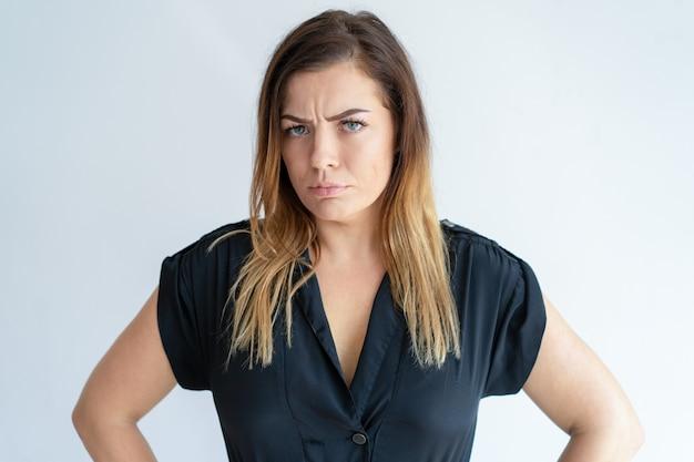 Сердитая симпатичная женщина смотрит на камеру и хмурится