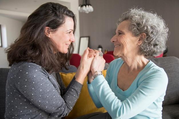 元気なシニア母親と彼女の娘が手を繋いでいます。