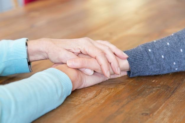 娘の手を握って年配の女性のクローズアップ