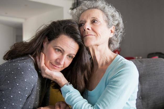 コンテンツの年配の女性と彼女の娘を抱きしめる