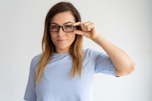 Довольная красотка поправляет очки и смотрит в камеру