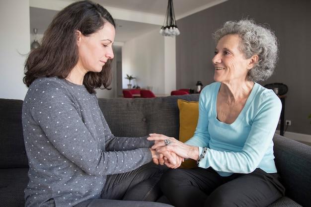 高齢者の女性と彼女の娘はチャットと手を繋いでいます。