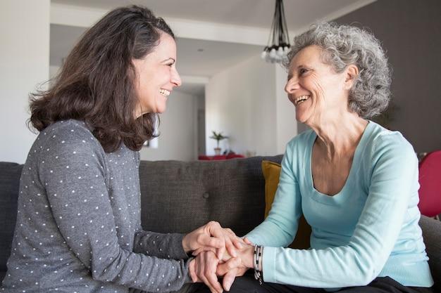 高齢者の女性と彼女の娘が笑っていると手を繋いでいます。