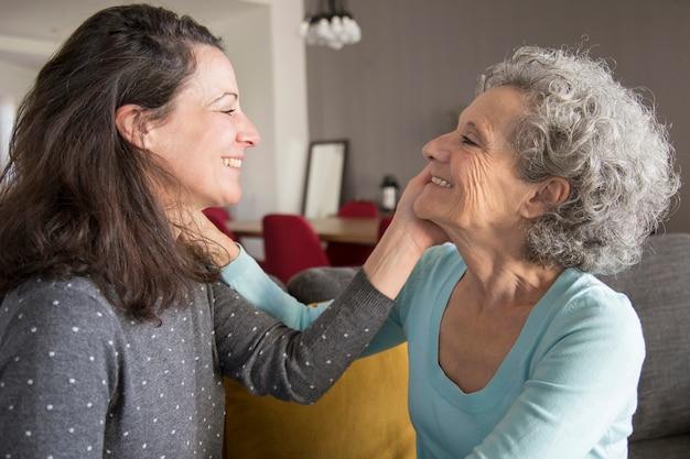 幸せな老人母と娘がお互いの顔に触れる