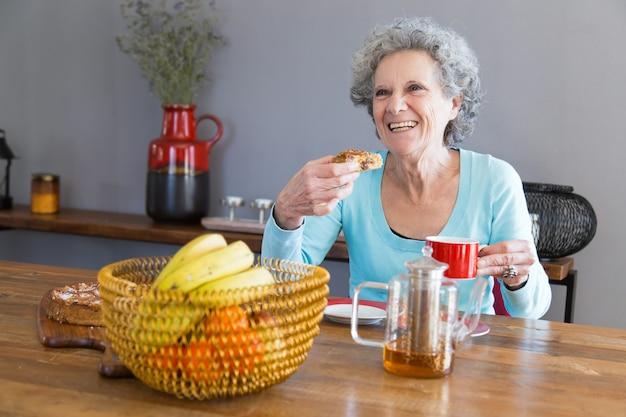 デザートを楽しんで幸せな年配の女性