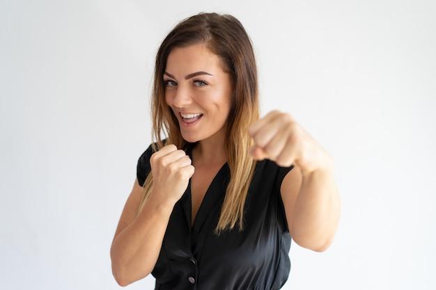 ボクシングのポーズで立っているうれしそうなきれいな女性