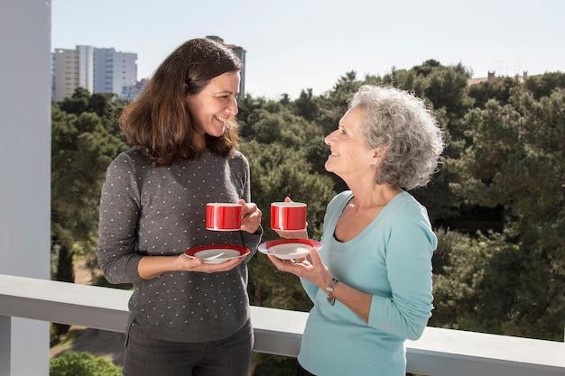 中年の女性が彼女の先輩母とバルコニーでお茶を飲む