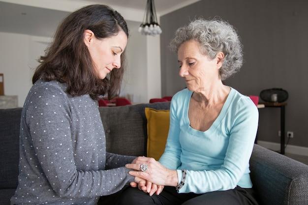 物思いにふける年配の女性と彼女の娘が手を繋いでいます。