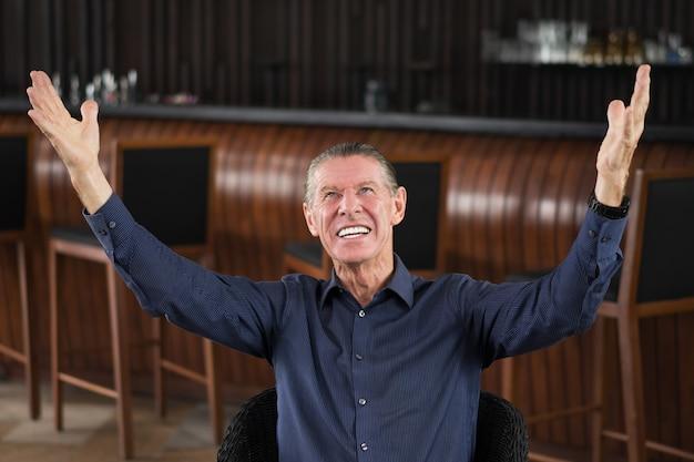 Счастливый старший человек, повышение руки в кафе