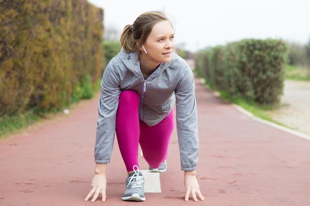 Задумчивая молодая женщина в стартовой позиции готова к бегу