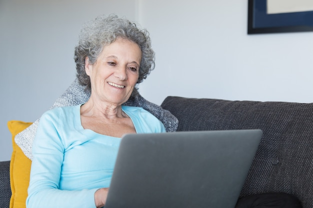 Портрет счастливой старшей женщины используя компьтер-книжку дома