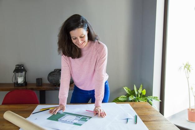 間取り図で働いている前向きな成功したアパートデザイナー