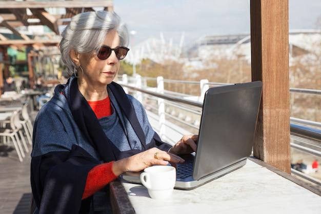 屋外カフェでコンピューターに取り組んでいる深刻な年配の女性