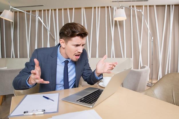 Возмущенный бизнесмен работает на ноутбуке в кафе