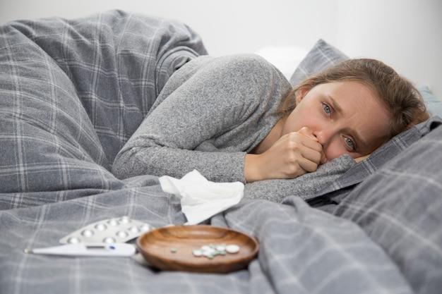 Больная молодая женщина лежит в постели, кашляет