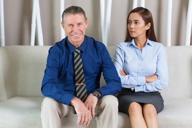 Мужские и женские деловые люди, сидя на диване