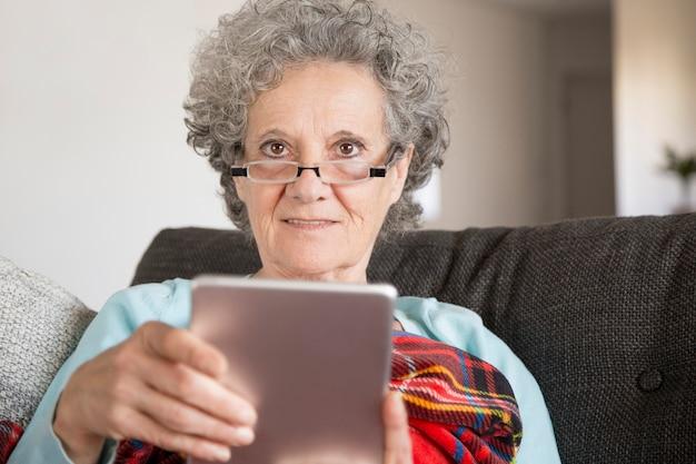 Улыбающаяся пожилая женщина в очках читает интернет-новости