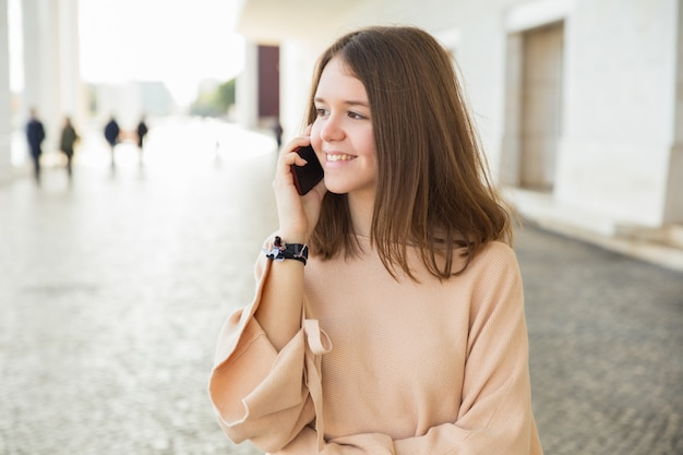 Улыбающаяся девушка подросток разговаривает по мобильному телефону на открытом воздухе