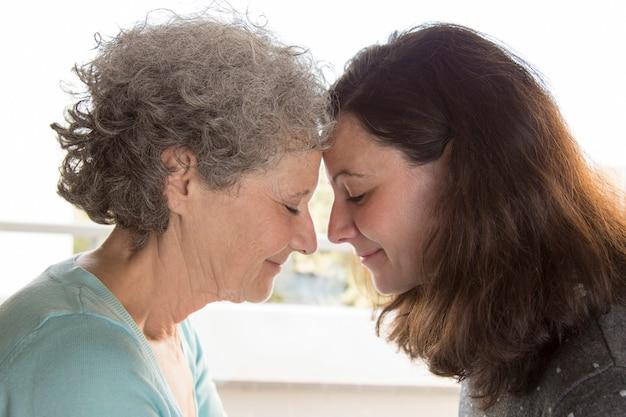 額に触れる先輩や中年の女性の笑顔