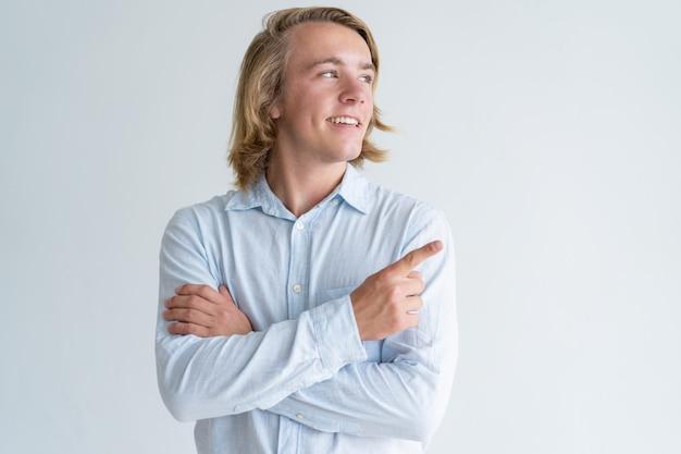 脇に指を指している若い男の笑みを浮かべてください。