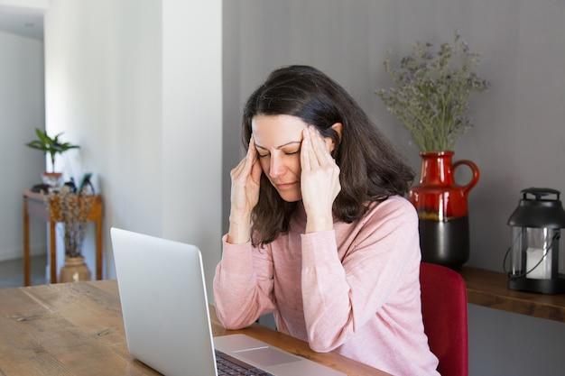 Усталый фрилансер страдает от головной боли
